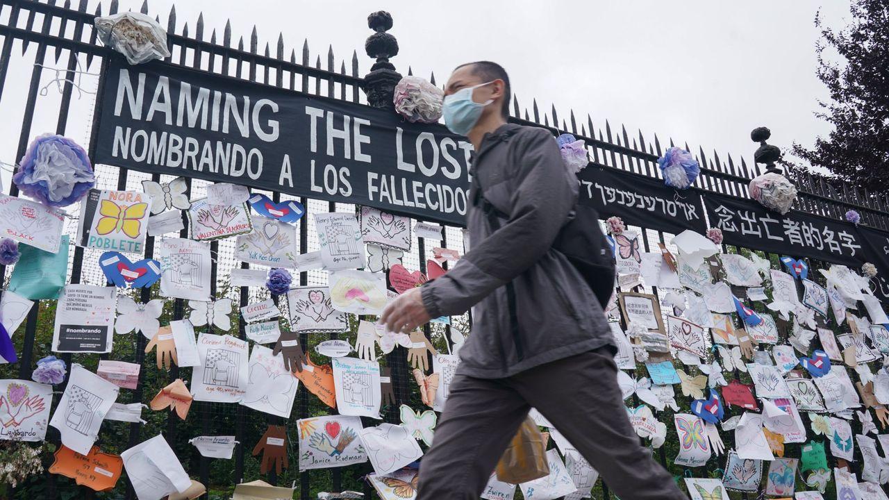 Un hombre camina con mascarilla por delante del homenaje a las víctimas del covid con la entrada de un cementerio en Nueva York
