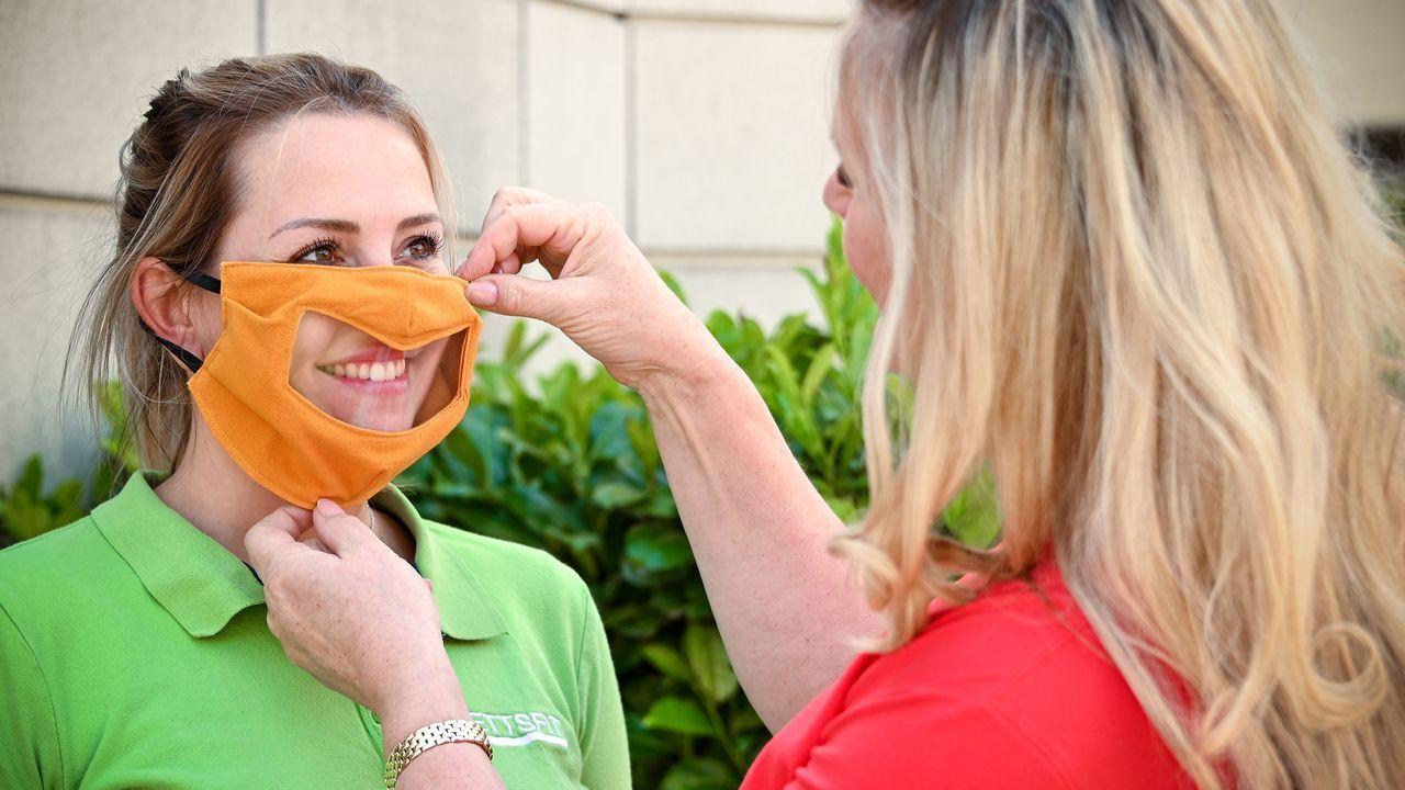 Nicole Lettermann (derecha en la imagen) ajusta a una empleada en Viersen, Alemania, una máscara con ventana que permite ver la expresión del rostro