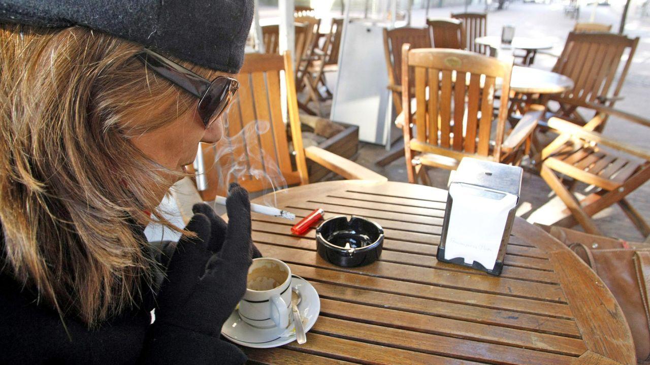 Una mujer, fumando en una terraza de Pontevedra. En Galicia solo se puede fumar en la vía pública si hay dos metros de distancia con el resto de personas