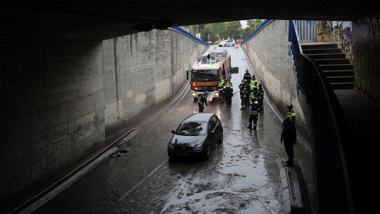 Efectivos del cuerpo de bomberos socorren a un vehículo que se ha quedado atrapado en un cruce bajo la A-5, en Madrid