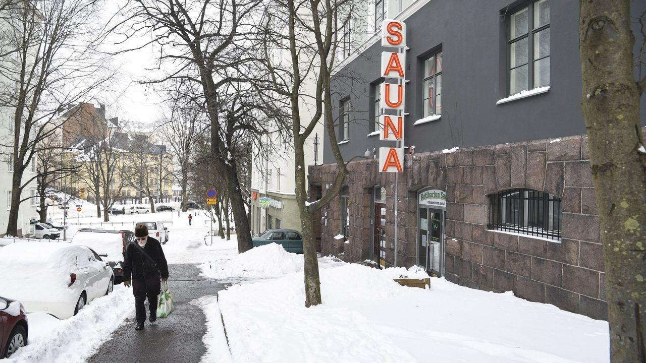 Un hombre, caminando con mascarilla por Helsinki