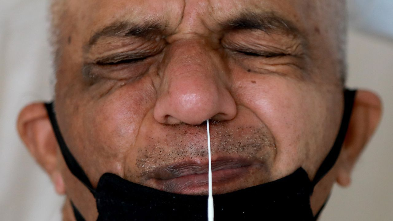 Un hombre que usa una máscara facial protectora reacciona cuando un médico introduce un hisopo en su nariz para detectar la enfermedad del coronavirus, en India