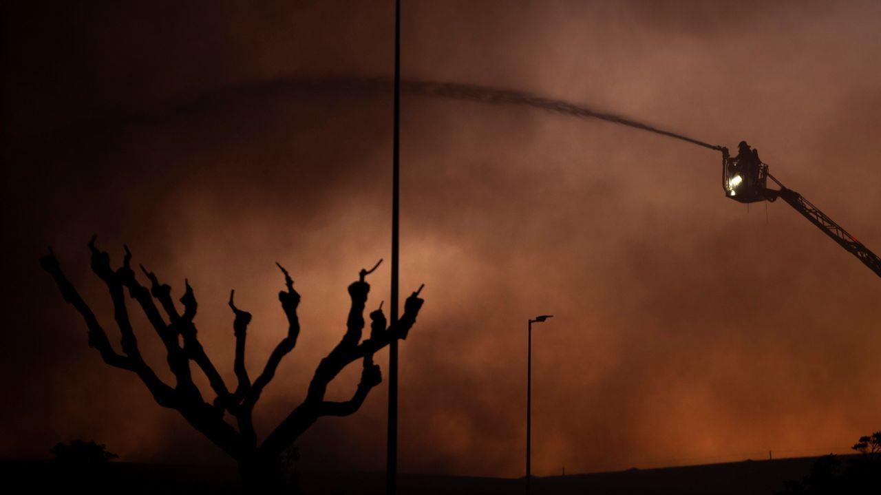Un bombero trabaja para apagar el incendio que afecta al museo histórico de Seat en Barcelona