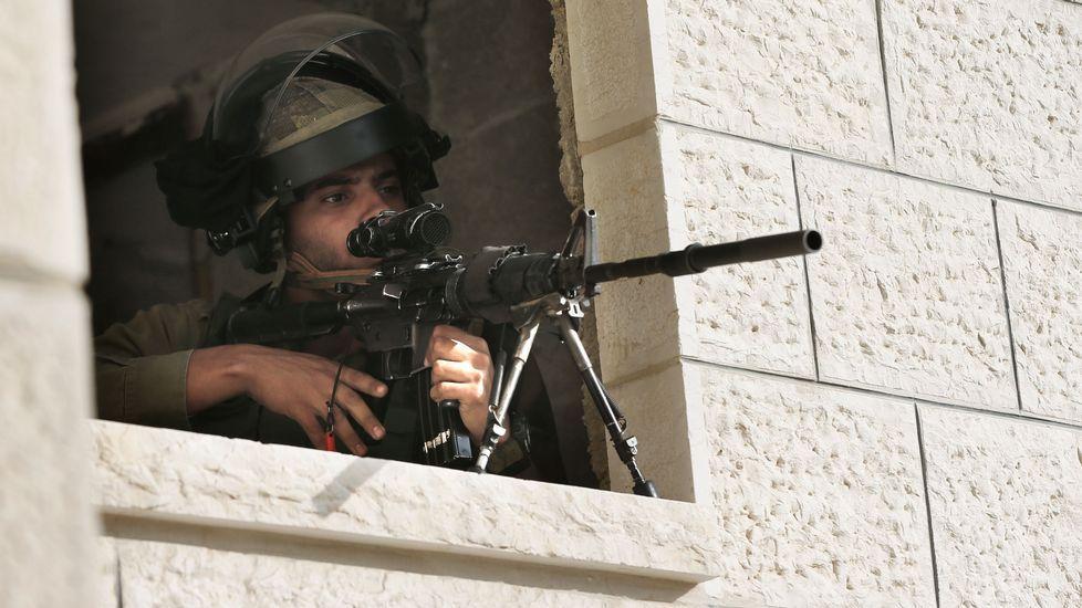 Un soldado israelí armado se prepara para abrir fuego desde una casa palestina.