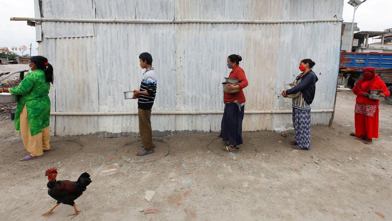 Un grupo de personas que espera para recibir comida en Kamandú respeta la distancia social