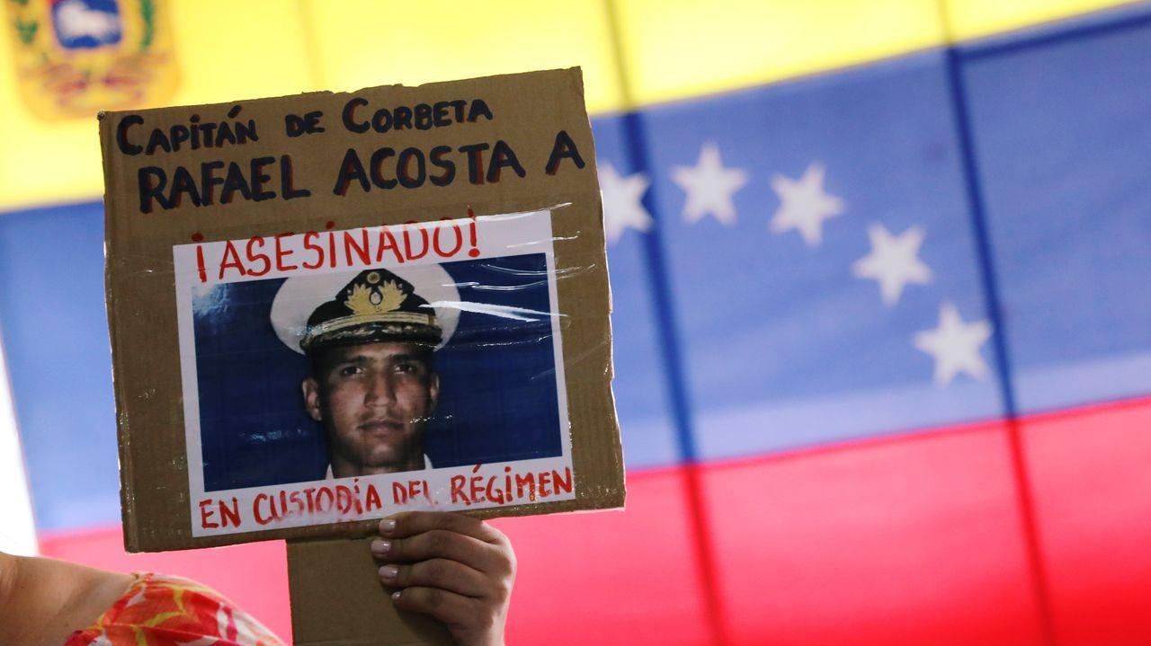 Una mujer sostiene un cartel con la imagen de Acosta.