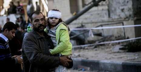 Los heridos evacúan la zona afectada por el coche bomba que explosionó frente a la Dirección de la Policía en El Cairo.