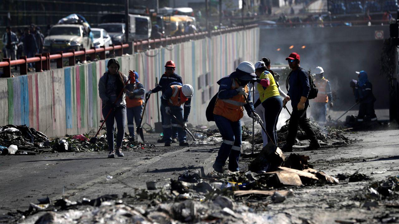 Ciudadanos, manifestantes indígenas y trabajadores limpian las calles de Quito, tras el fin de las protestas