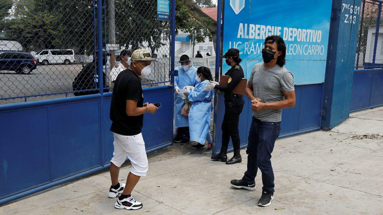 Dos ciudadanos guatemaltecos aguardan para someterse al test de temperatura para acceder a un albergue, después de haber sido deportados desde Estados Unidos