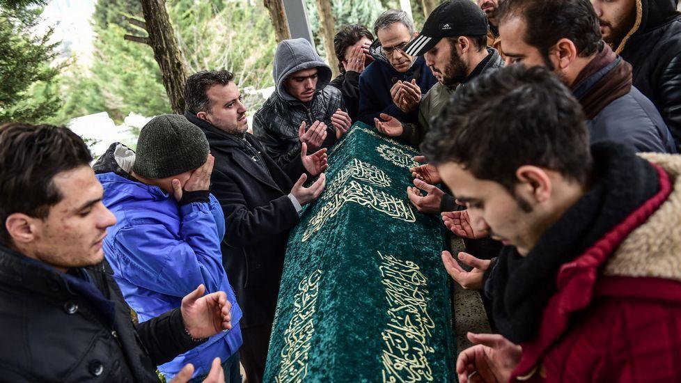 Varias personas rezan ante el féretro de Mohamed Elhot, una de las víctimas mortales del ataque a la discoteca de Estambul.