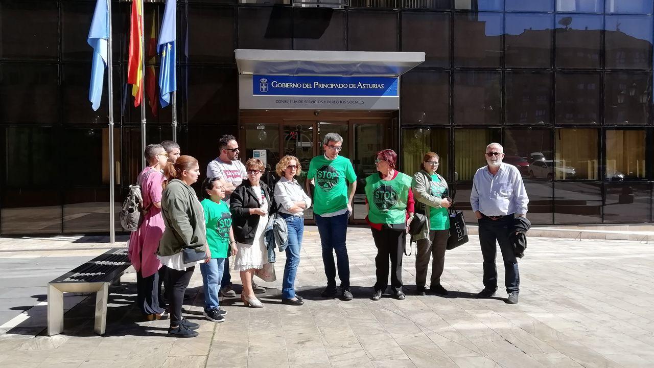 Los protestantes junto con la familia delante de la Consejería de Servicios y Derechos Sociales