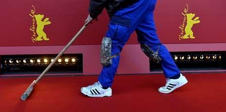 Berlinale: el festival que inaugura el glamour.Un trabajador limpia la alfombra roja de la Berlinale.