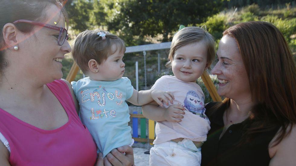 Dos madres hablan entre ellas con sus hijos en brazos
