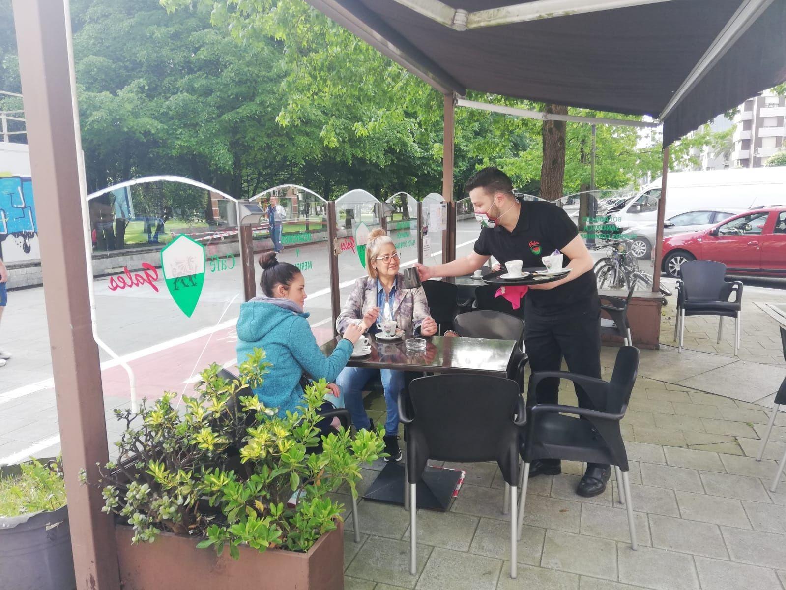 Eduardo González, propietario del café Galés, sirve unos cafés a unas clientas en su terraza