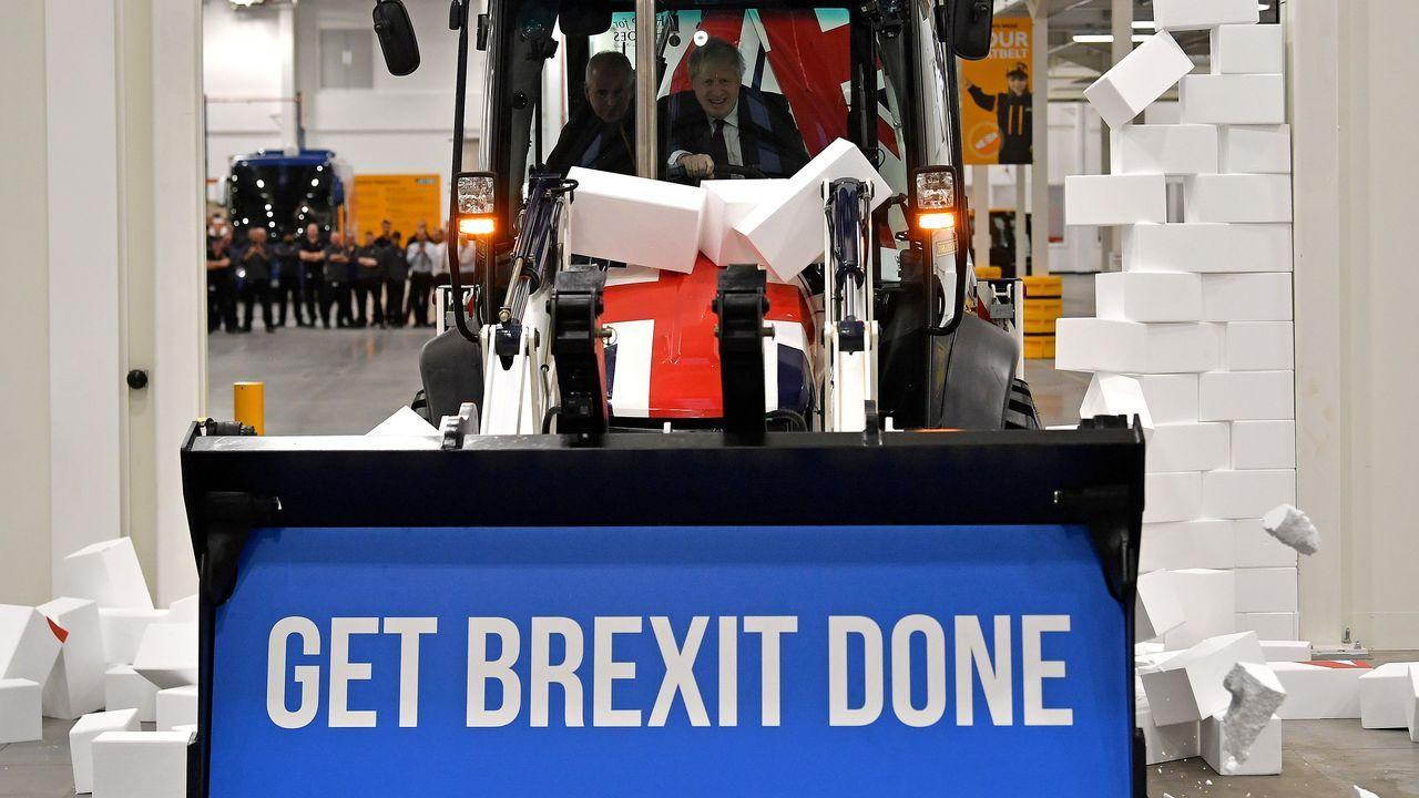 Boris Johnson derriba un falso muro con una excavadora con su lema de campaña