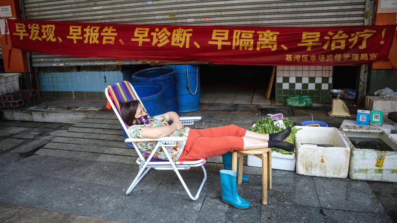 Una mujer, con mascarilla, duerme la siesta en el mercado húmedo de Guangzhou, China