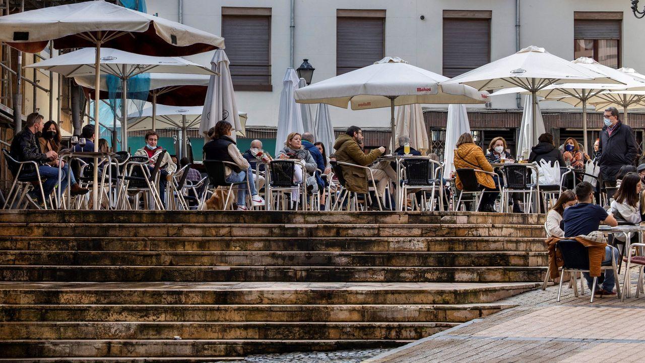 Paseantes en Oviedo. Varias personas disfrutan de la terraza de un bar