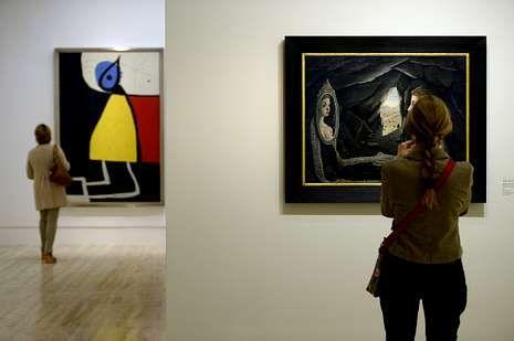 Una obra de Delvaux y otra de Miró, al fondo, en la muestra.