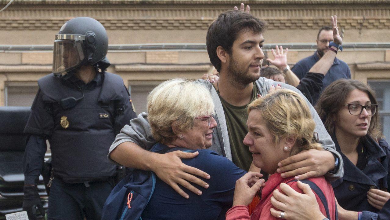 Varias personas lloran en el exterior de un instituto en L'Hospitalet de Llobregat.