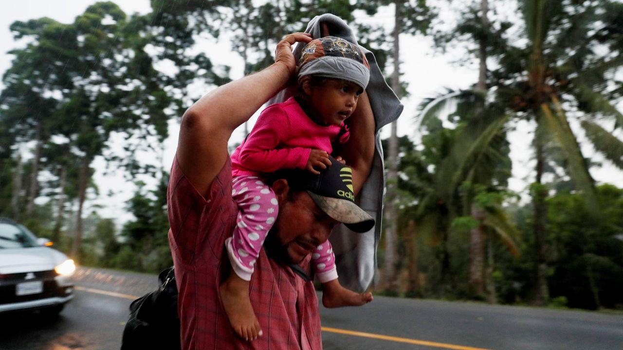 Un migrante hondureño trata de cubrir de la lluvia a su hija mientras camina por una carretera de Guatemala en dirección a Mexico