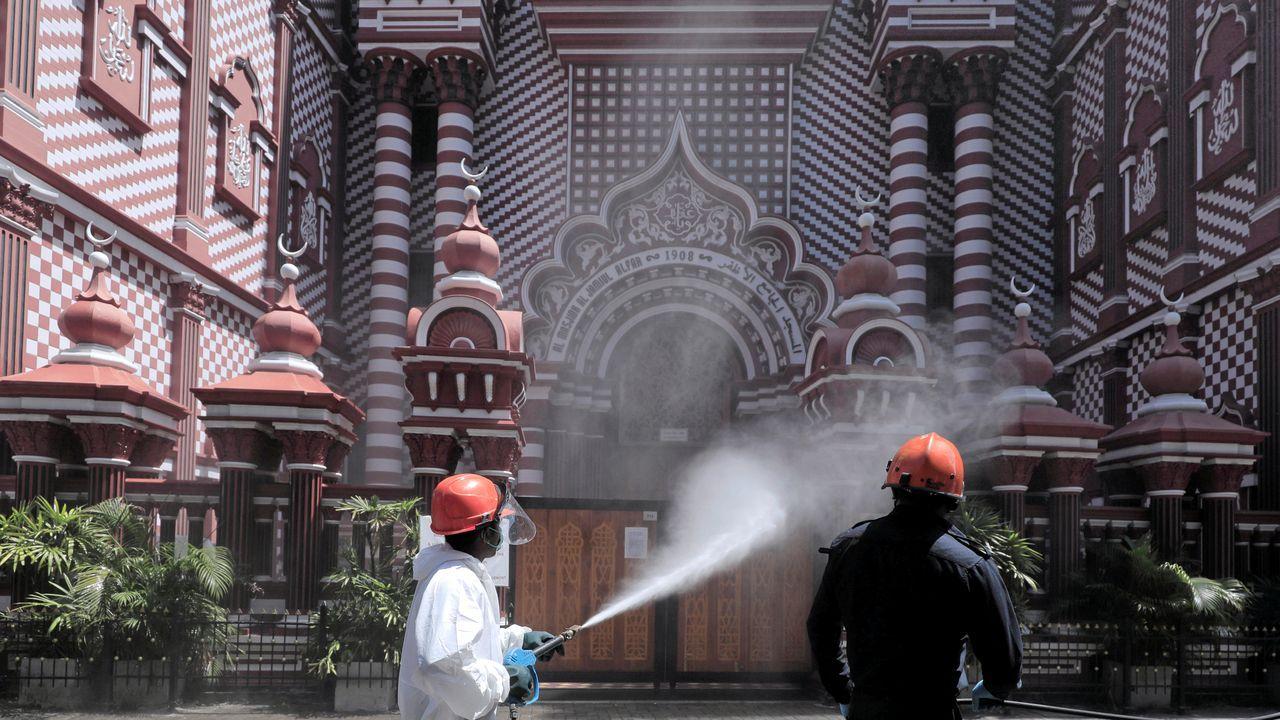 Un bombero rocía desinfectante en una calle de Sri Lanka