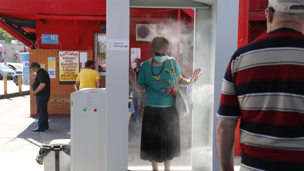 En Tiblisi, la capital de Georgia, una mujer pasa por un arco desinfectante en una estación de autobuses