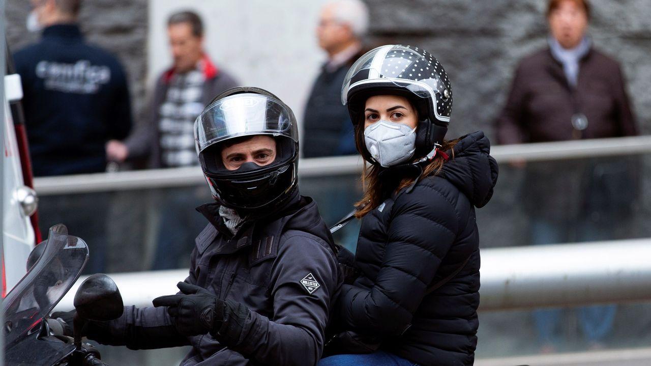 Una pareja pasa en una motocicleta ante las personas que hacen cola para comprar de alimentos y productos básicos en un supermercado en el centro de Barcelona, este sábado en el que España entra en estado de alarma para movilizar al máximo los recursos necesarios para combatir el COVID-19