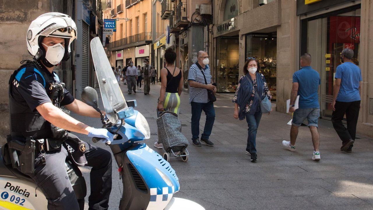Avilesinos con discapacidad recorren el casco antiguo en silla de ruedas.Un policía vigila las calles de Lérida, donde se produjo un rebrote