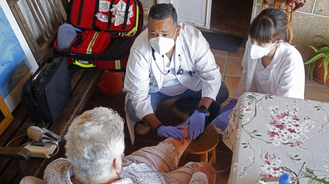 El doctor Albert Fo y la enfermera Lucía, del centro de salud de Piñor, atienden a una paciente en su domicilio