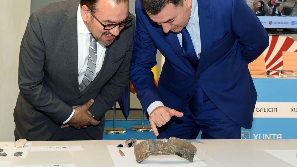 El rector de la USC, Antonio López —izquierda— y el conselleiro de Cultura, Román Rodríguez, observan los restos de la vasija prehistórica encontrada en el yacimiento arqueológico de Triacastela