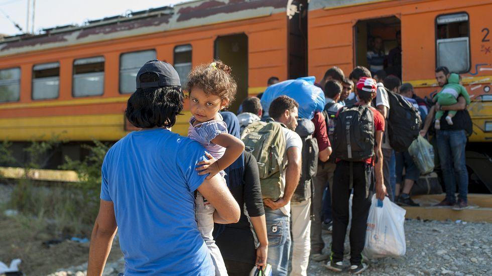 Inmigrantes se suban a un tren con destino a Serbia en la frontera entre Grecia y Macedonia, en la ciudad de Gevgelija