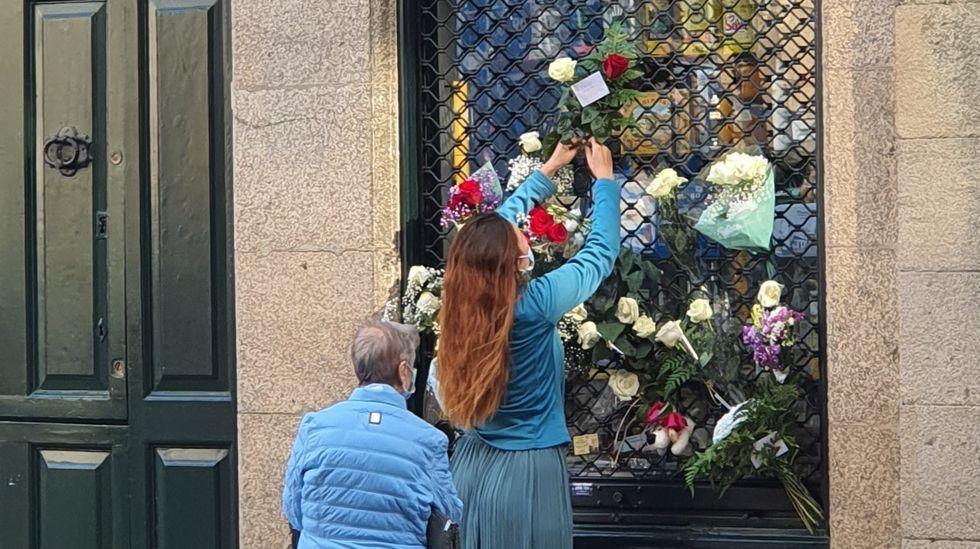 Unas mujeres colocan flores en el ultramarinos que la familia Cepeda regenta en la plaza de Cervantes
