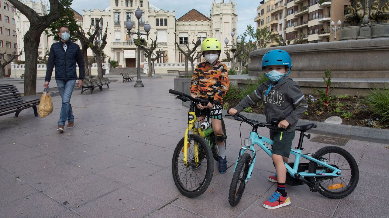 Unos niños en bicicleta pasean hoy con su padre por la calle Fatás y la plaza Navarra de Huesca