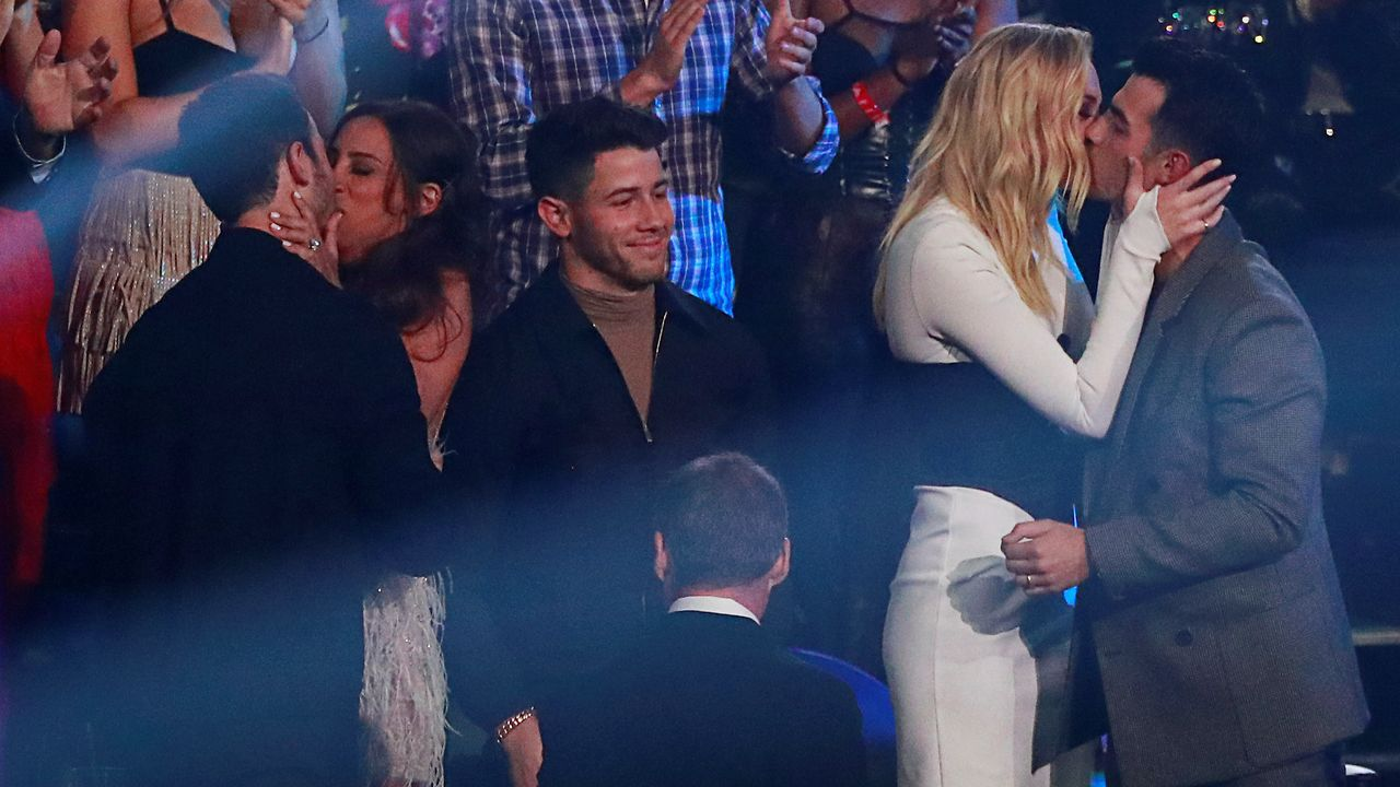 Jonas Brothers celebrando junto a sus parejas su premio