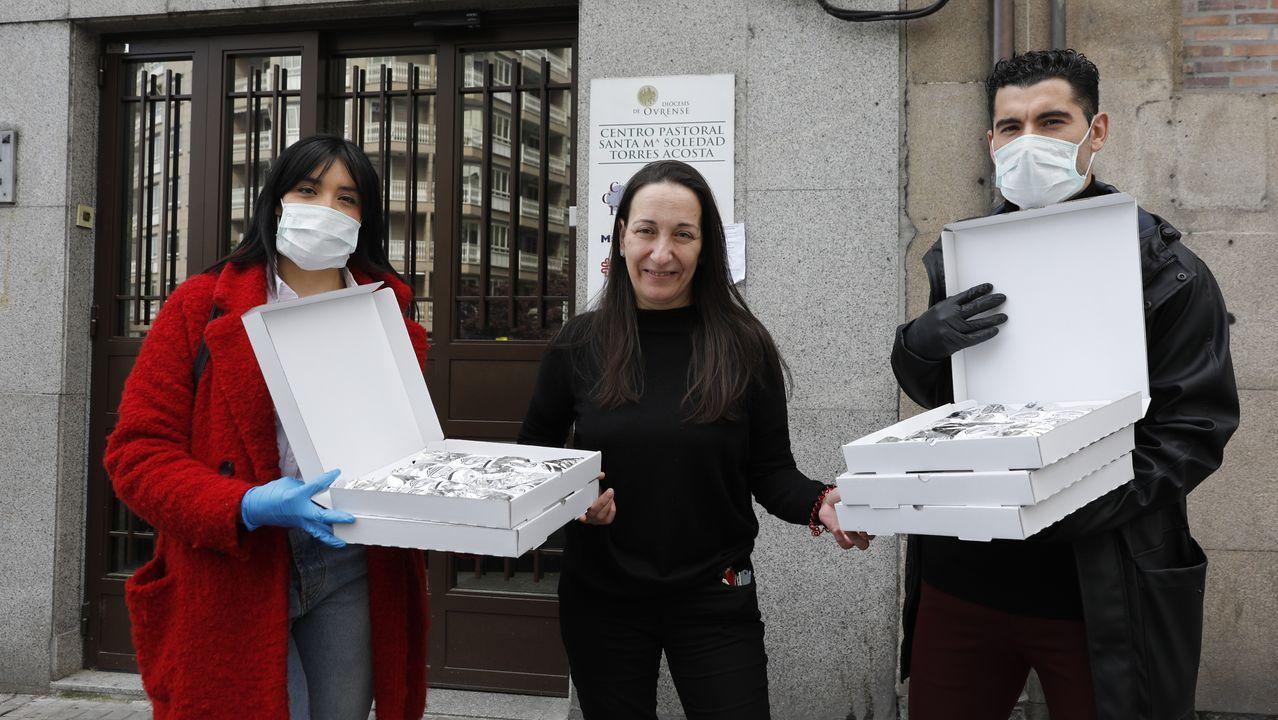 Carla Quintela y Álex Fernández entregan la donación de burritos a la responsable del comedor de Cáritas, Ana Vázquez (en el medio).