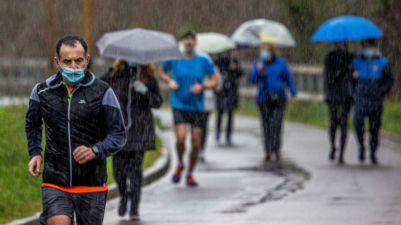 Vecinos de Oviedo hacen deporte bajo la lluvia