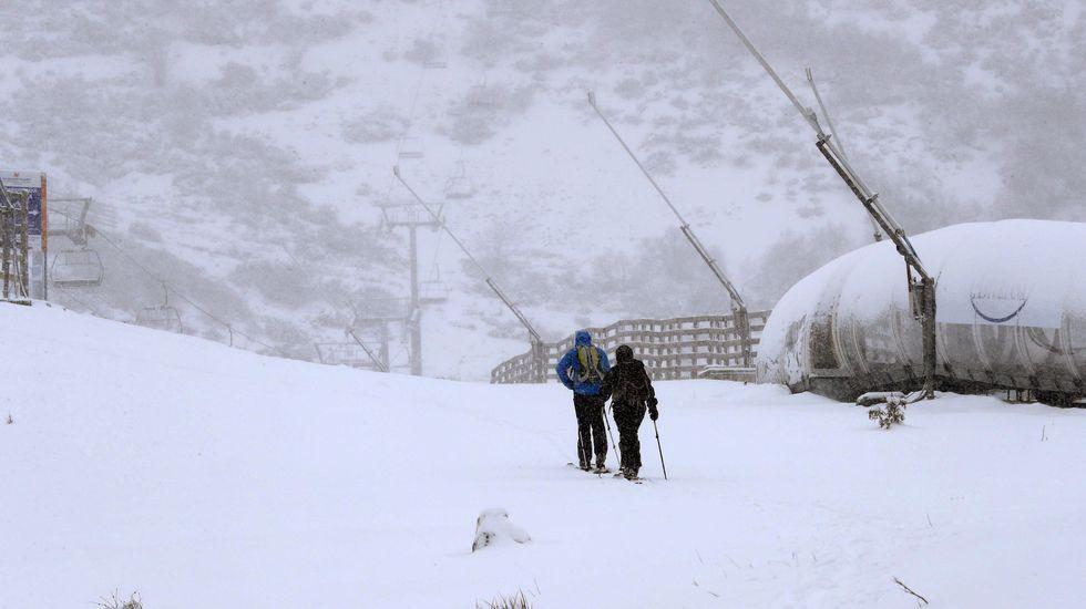 Los esquiadores disfrutan de la nieve con la estación de esquí de Valgrande-Pajares al fondo.Estacion de esqui de Pajares