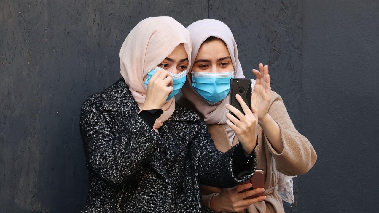 Dos mujeres, ataviadas con mascarillas, con su teléfono en Londres