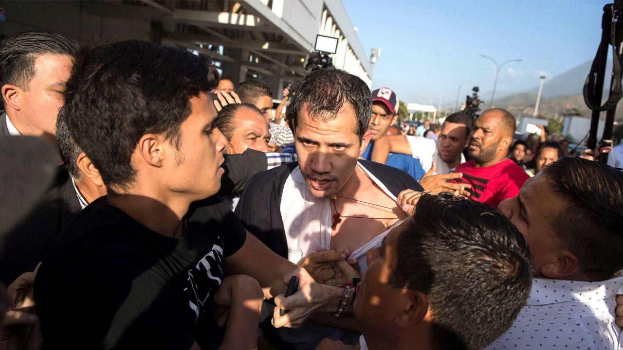 Guaidó intenta zafarse de los seguidores chavistas que le esperaban a la salida de la terminal en Caracas