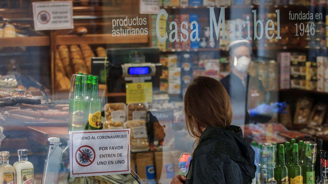 Una mujer observa el escaparate de una tienda de productos típicos, cuyo cartel informa sobre la entrada limitada en el local, en Oviedo.