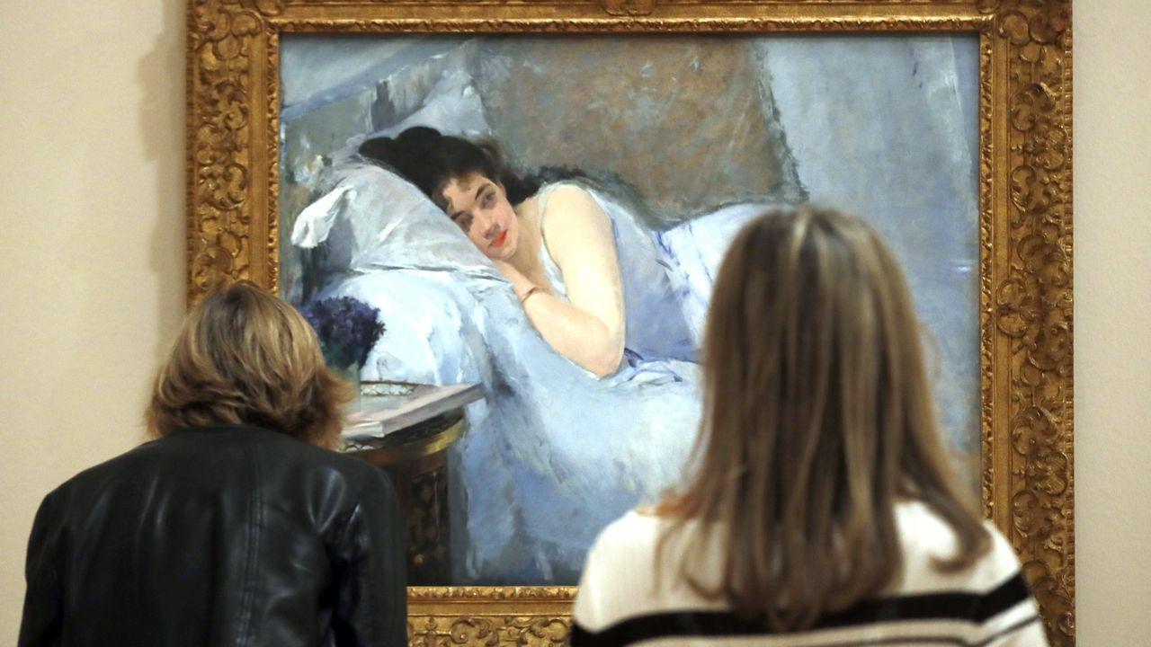 Dos visitantes observan el retrato que Eva Gonzalès hizo de su hermana
