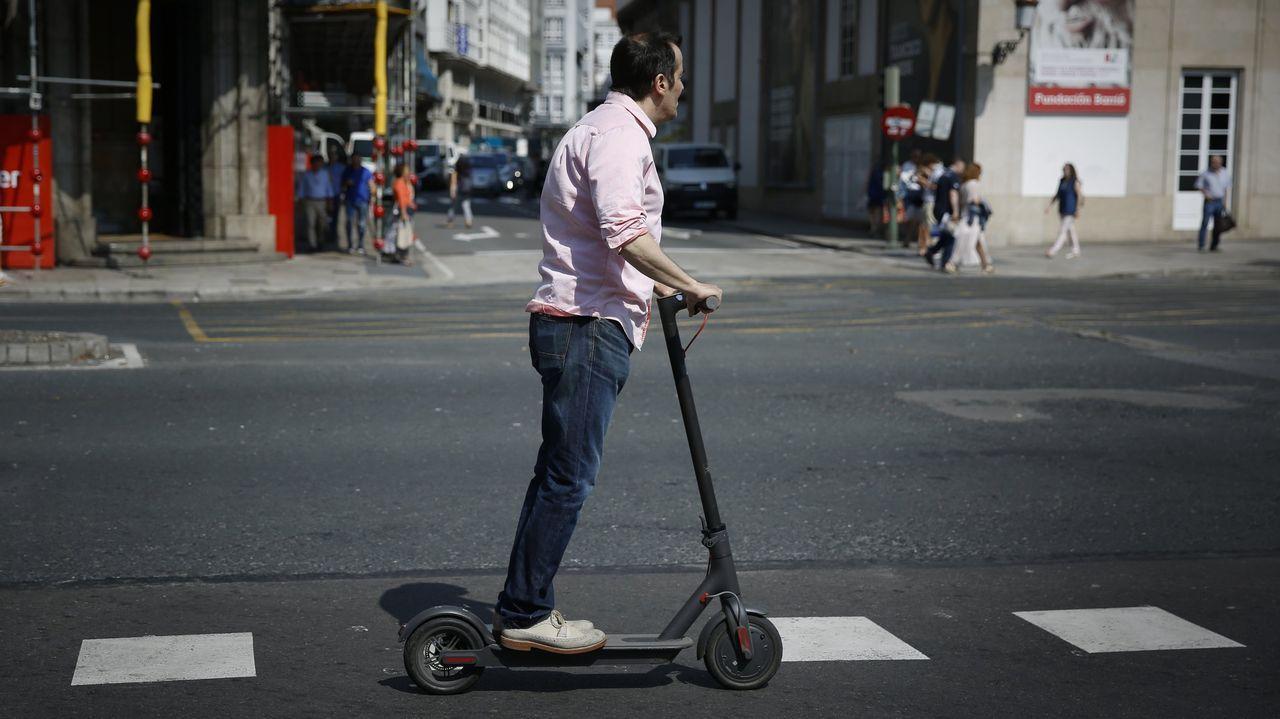 Usuario circulando en patinete por una calle de A Coruña