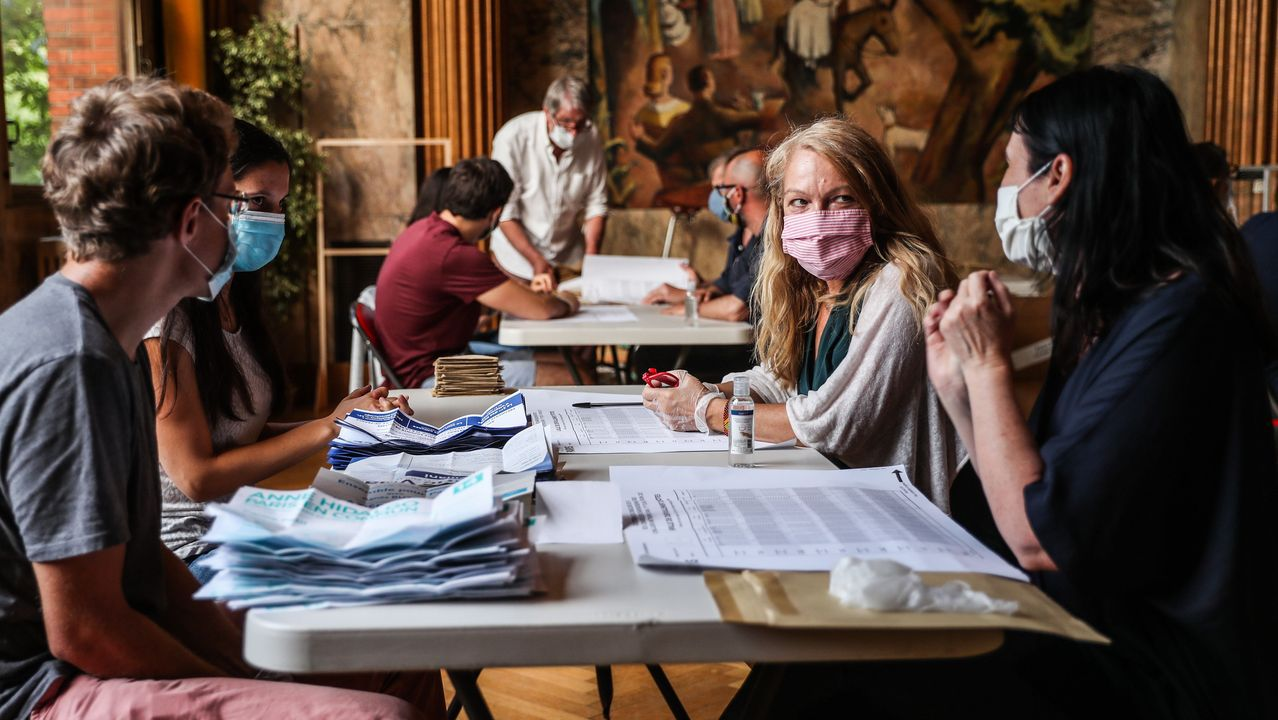 Voluntarios con máscaras en un colegio electoral de París