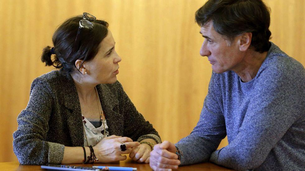 La consejera de Hacienda, Dolores Carcedo (i), y el diputado de Podemos, Enrique López (d), conversan durante el pleno de hoy de la Junta General del Principado