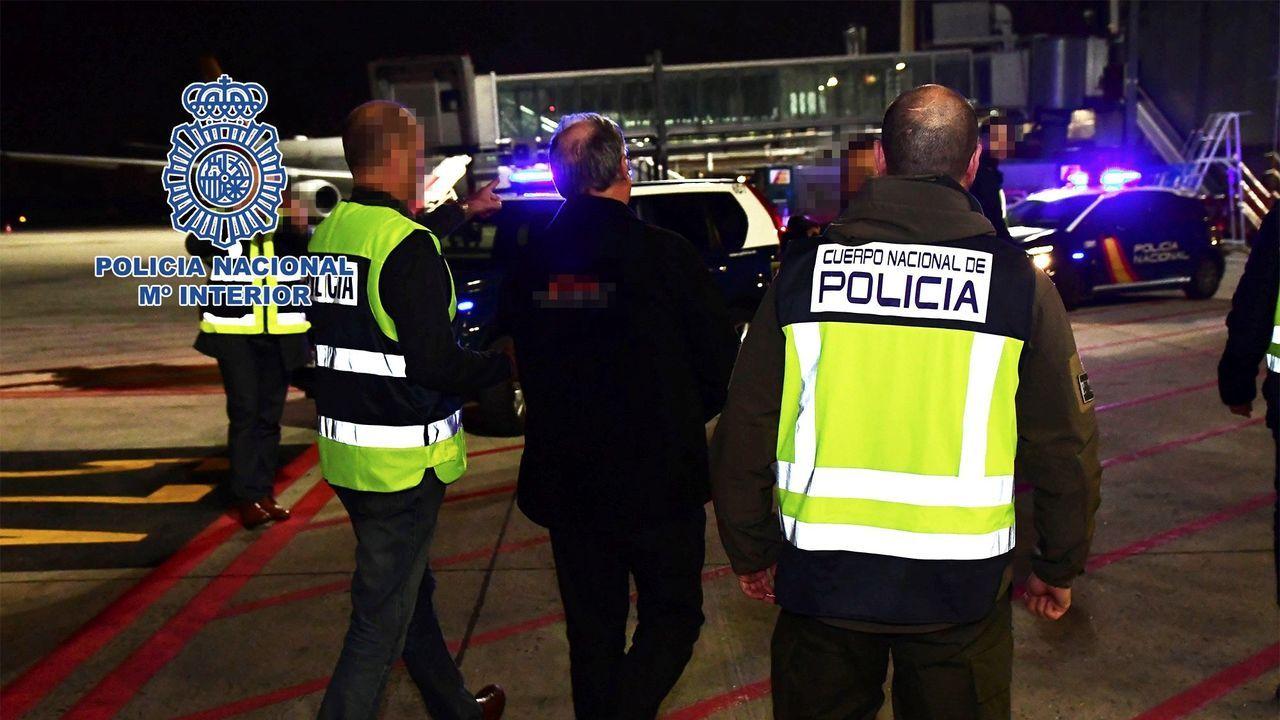 dos agentes de policía mientras escoltan a Carlos García Juliá (c), uno de los autores de la matanza de Atocha de 1977, tras ser extraditado por Brasil, en febrero de este año
