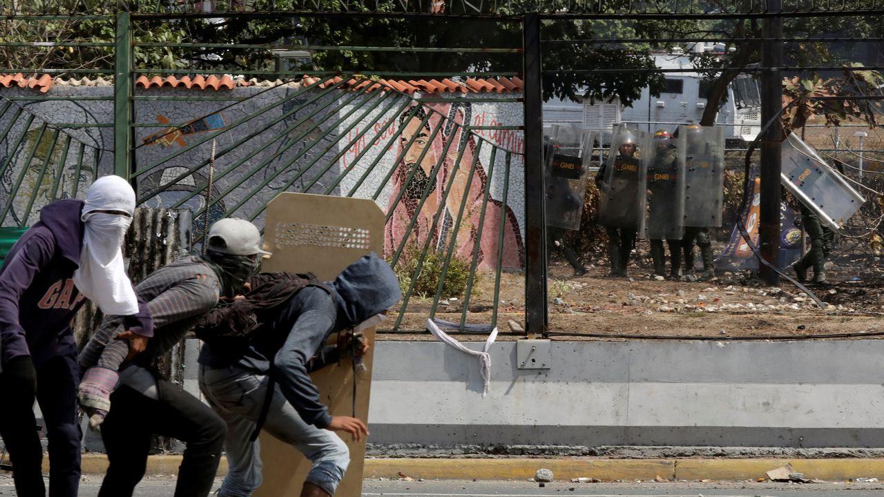 Un grupo de opositores se protege frente a agentes de la Guardia Nacional Bolivariana