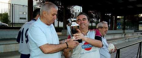 Germán Gamallo, del equipo del INSS, entrega el trofeo Perpetuo Socorro, al portero de O Chopo.