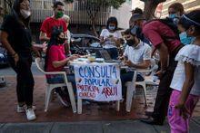 Un grupo de personas se informan sobre la consulta popular, este jueves, en Caracas
