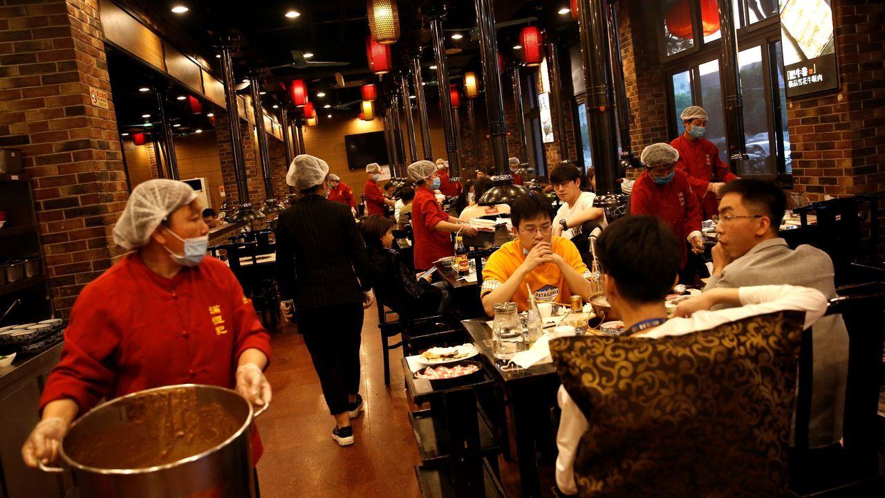 En Pekín los trabajadores de los restaurantes trabajan con mascarillas, guantes y gorros plásticos