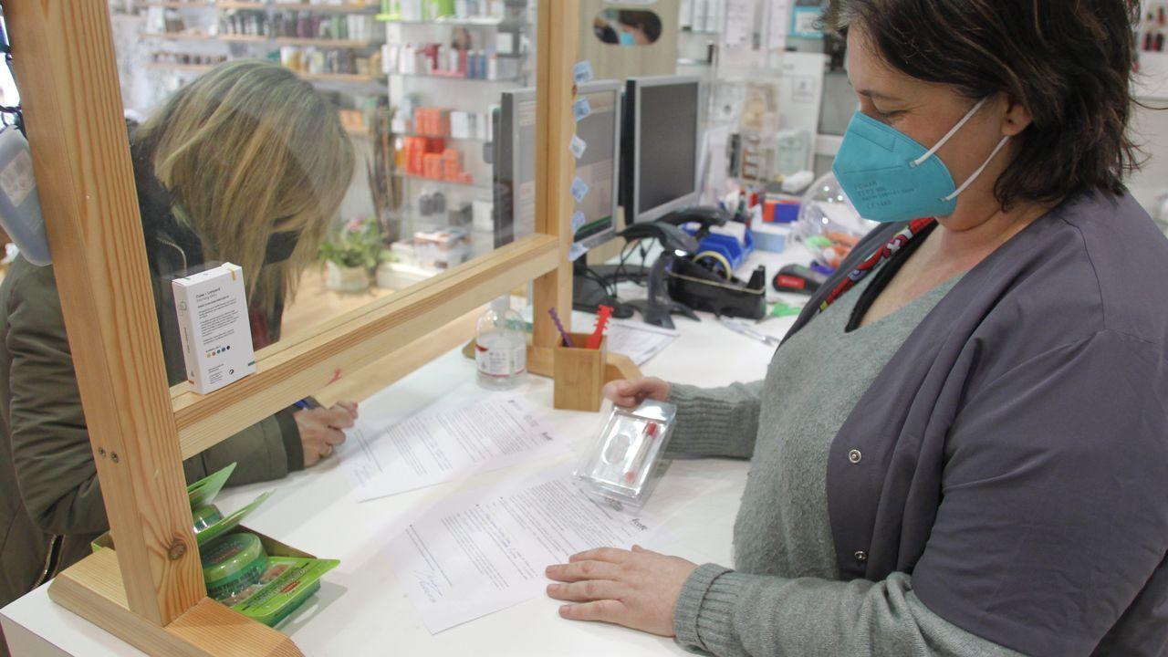 La visita de la reina Sofía al Banco de Alimentos.En la imagen, una madre firma el consentimiento informado en el momento de recoger el kit para la muestra en la farmacia de María Adrio